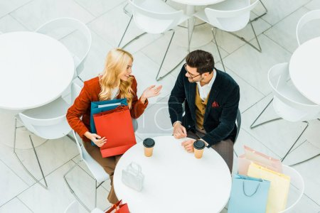 Photo for Overhead view of beautiful happy couple with shopping bags talking and sitting in cafe - Royalty Free Image