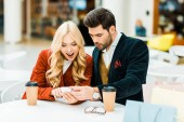 excited couple using smartphone in cafe with coffee to go and shopping bags
