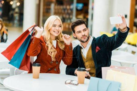 Photo pour Couple à la mode avec des sacs à provisions et café pour aller prendre selfie sur smartphone dans centre commercial - image libre de droit