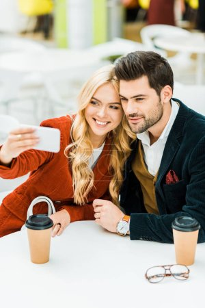 beautiful couple with coffee to go taking selfie on smartphone in cafe