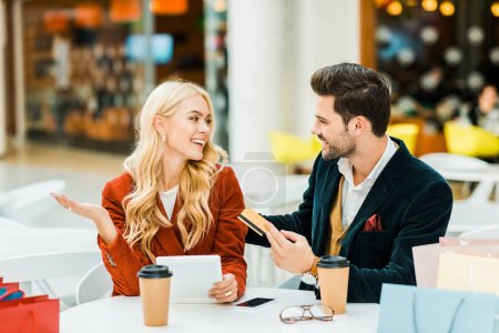 Photo for Happy stylish couple shopping online with credit card and tablet while sitting in cafe in shopping center - Royalty Free Image