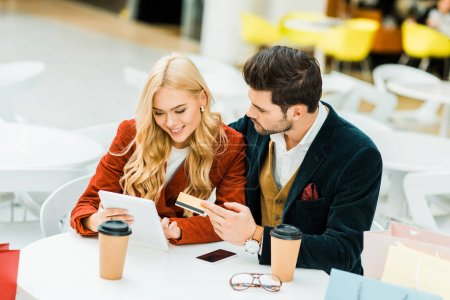 Photo for Smiling couple shopping online with credit card and digital tablet while sitting in cafe in shopping mall - Royalty Free Image