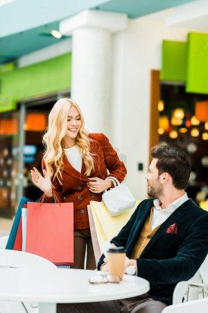 beautiful girl with shopping bags waving to boyfriend in cafe in shopping center