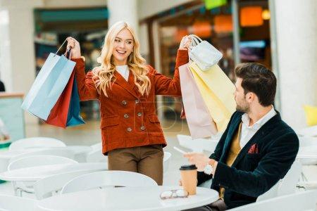 happy shopaholic showing shopping bags to boyfriend in cafe in shopping center
