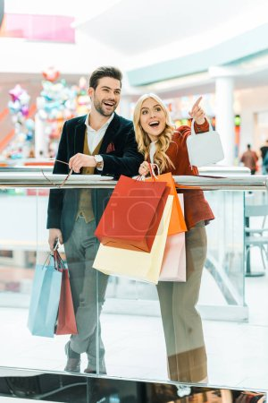 Photo for Young couple with shopping bags spending time in shopping mall, woman showing something - Royalty Free Image