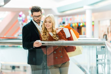 young stylish couple with shopping bags using smartphone in shopping mall
