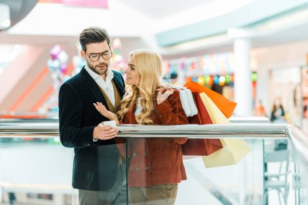 Photo for Beautiful stylish couple with shopping bags using smartphone in shopping center - Royalty Free Image