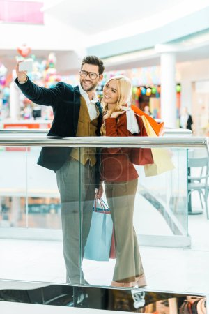 smiling fashionable couple with shopping bags taking selfie in shopping mall