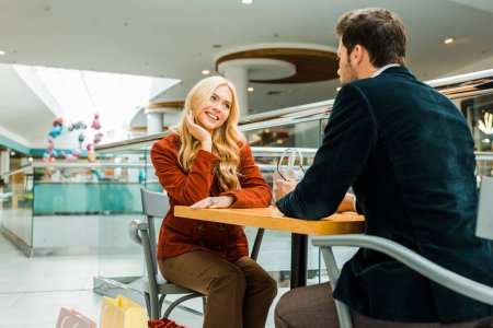 Photo for Happy couple looking at each other and sitting with shopping bags in cafe in mall - Royalty Free Image