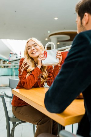 happy attractive woman showing bag with sale tag to boyfriend in shopping mall