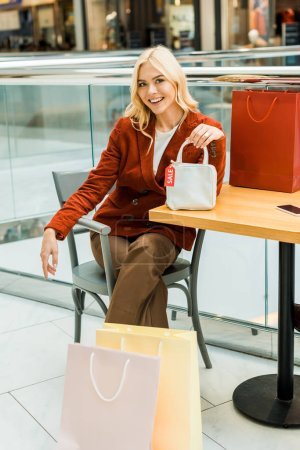 smiling blonde girl sitting in mall with shopping bags and one bag with sale tag