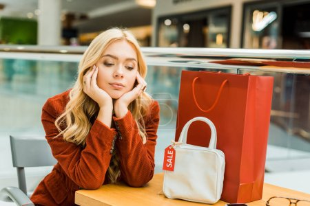 upset woman sitting in mall with one shopping bag and one bag with sale tag