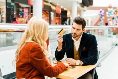 beautiful fashionable couple shopping online with credit card and smartphone