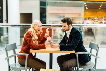 Photo for Excited couple shopping online with credit card and smartphone - Royalty Free Image