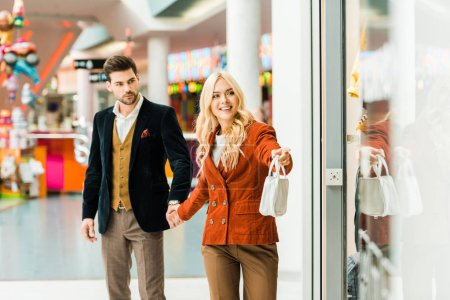 Photo for Young beautiful woman showing showcase to boyfriend in shopping center - Royalty Free Image