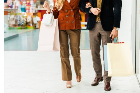 Photo for Cropped view of young couple with shopping bags walking in shopping mall - Royalty Free Image