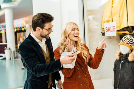 excited girl pointing at super sale with 70 percents discount on showcase in shopping center