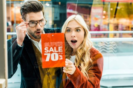 beautiful excited couple of shopaholics looking at super sale with 70 percents discount in shopping center