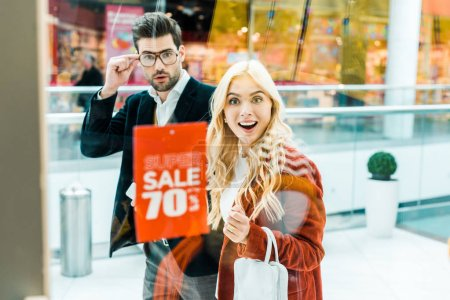 surprised couple looking at super sale with 70 percents discount in shopping center