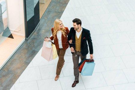 Photo pour Vue aérienne du jeune couple des accros du shopping avec des sacs à pied au centre commercial - image libre de droit