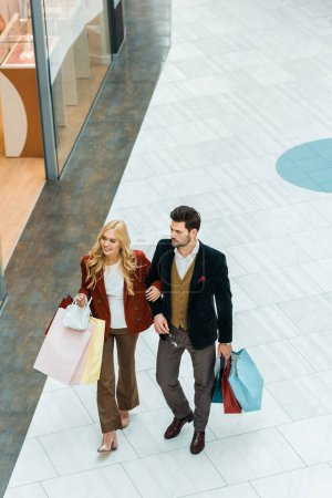 overhead view of young customers with shopping bags walking in shopping mall