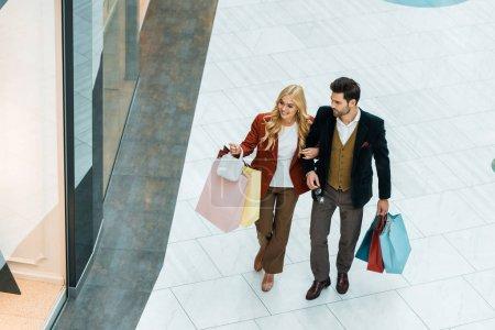 Photo pour Vue aérienne du jeune couple avec des sacs à provisions à pied au centre commercial - image libre de droit