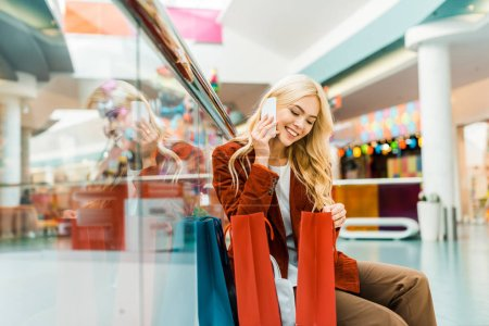 Photo for Smiling shopaholic talking on smartphone and looking into shopping bags - Royalty Free Image