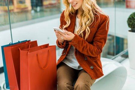 Photo pour Vue recadrée de la femme en utilisant un smartphone et assis avec des sacs à provisions - image libre de droit