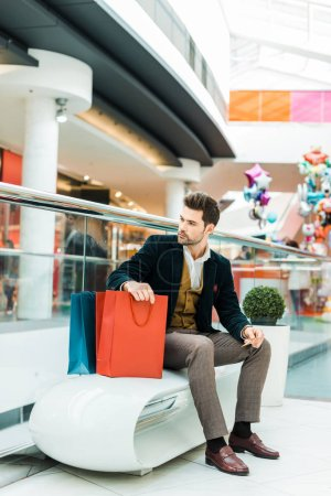 fashionable man holding credit card and sitting with bags in shopping center