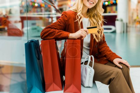cropped view of blonde woman holding credit card and sitting with shopping bags in mall