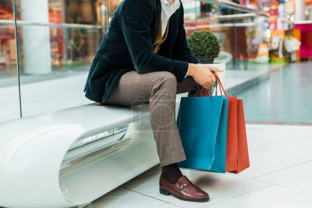 cropped view of stylish man holding shopping bags and sitting in mall