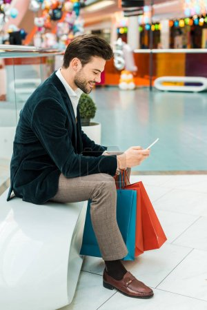 fashionable man using smartphone in shopping center with bags
