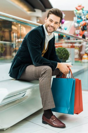 happy stylish man holding shopping bags in mall