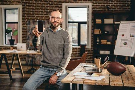 Photo pour Vue recadrée de l'homme d'affaires occasionnel tenant smartphone avec écran blanc dans le bureau loft - image libre de droit
