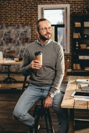 Photo for Casual businessman sitting at desk and holding cup of coffee in loft office - Royalty Free Image