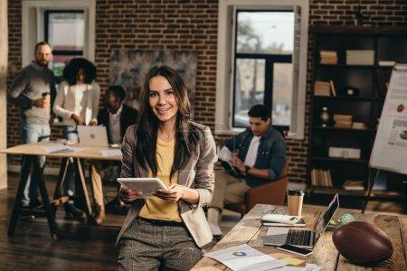 Photo pour Femme d'affaires occasionnel souriant tenant la tablette dans Bureau loft avec des collègues de travail derrière - image libre de droit
