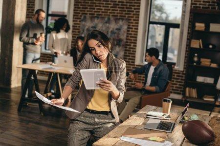 Photo pour Femme d'affaires occasionnelle occupée travaillant et parlant sur smartphone dans le bureau loft avec des collègues derrière - image libre de droit