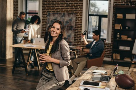 smiling casual businesswoman holding coffee in loft office with colleagues working behind