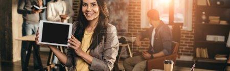 Photo pour Vue recadrée sur tablette tenue casual femme d'affaires avec un écran blanc au bureau loft avec rétro-éclairé et ses collègues de travail derrière - image libre de droit