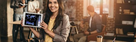 Photo for Cropped view of happy casual businesswoman holding tablet with graph on screen in loft office with colleagues working behind - Royalty Free Image