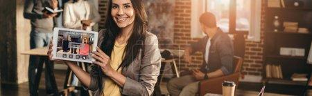 Photo pour Vue recadrée de tablette tenue femme casual heureux avec graphique sur écran au bureau loft avec des collègues de travail derrière - image libre de droit