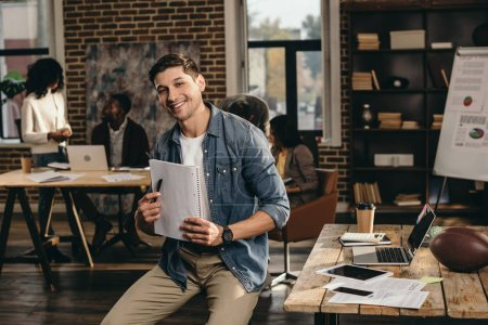 smiling young man looking at camera, holding pen and journal in modern loft office with colleagues working on background