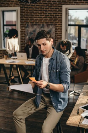 young man holding journal and looking at note in modern loft office with colleagues working on background