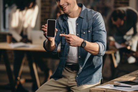 Photo pour Vue recadrée du jeune homme souriant pointant du doigt sur smartphone dans le bureau loft moderne avec des collègues en arrière-plan - image libre de droit