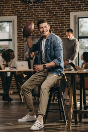 happy young man holding rugby ball in modern loft office with colleagues on background