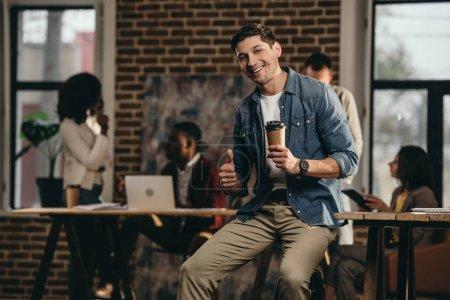 Photo pour Jeune homme tenant café et donnant des pouces vers le haut de signe au bureau loft moderne avec ses collègues sur fond - image libre de droit