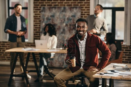 african american casual businessman drinking coffee with colleagues working behind in loft office
