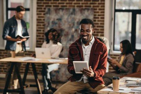 Photo pour Souriant afro-américain occasionnel homme d'affaires tenant tablette avec des collègues travaillant derrière dans le bureau loft - image libre de droit