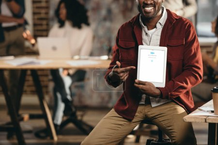 cropped view of smiling african american casual businessman holding tablet with skype app and colleagues working behind in loft office