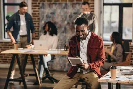 smiling african american casual businessman holding tablet with colleagues working behind in loft office